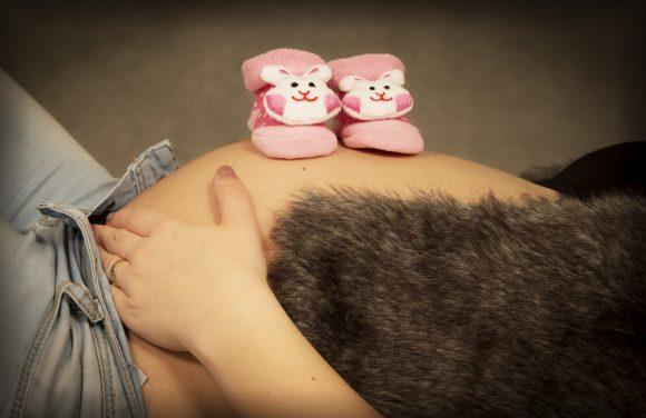 Babybauch mit Kinderschuhen